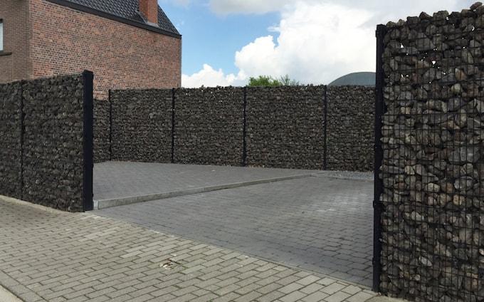 Steenkorven tuinafsluiting met zwarte metalen palen